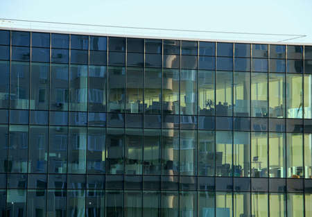 work places: Panoramic windows of the office building with work places inside
