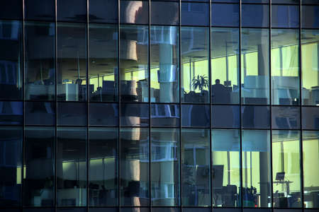 company building: Clear windows of the office building with work places inside
