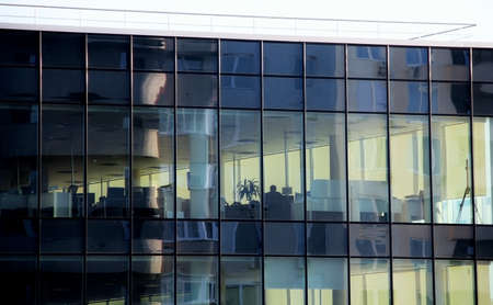 work places: Clear windows of the office building with work places inside