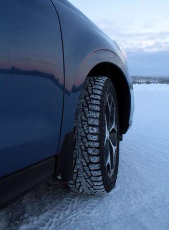 Beslagen sneeuwbanden op de auto bij de winterweg