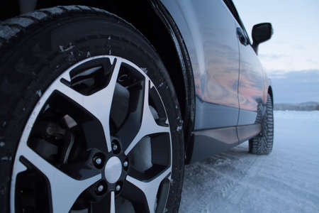 tyre tread: Studded snow tires on the car at winter road