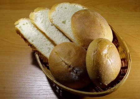 breadbasket: Hot baking bread. Round wheat buns and sliced bread in straw breadbasket