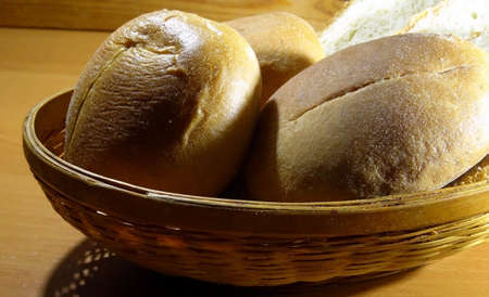 sliced bread: Hot baking bread. Round wheat buns and sliced bread in straw breadbasket