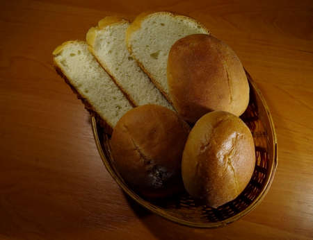 breadbasket: Slices of loaf and round buns in wicker breadbasket