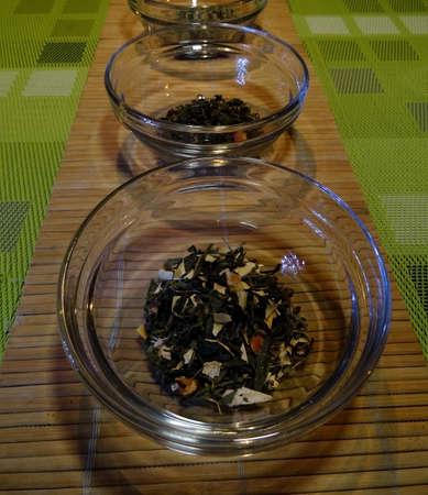 servilleta de papel: Juego de té. de hojas sueltas tés verdes en copas en la servilleta mesa de mimbre Foto de archivo