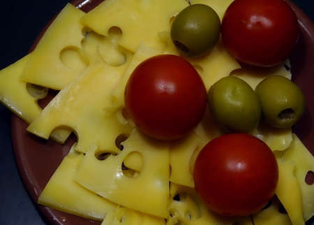 swiss cheese: International cuisine. Spanish olives, swiss cheese and italian tomatoes on clay plate