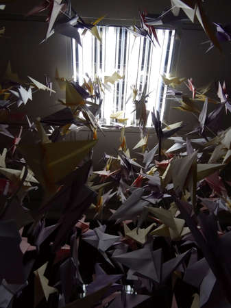 techiques: Handmade colored origami cranes on ceiling strings under light lamp