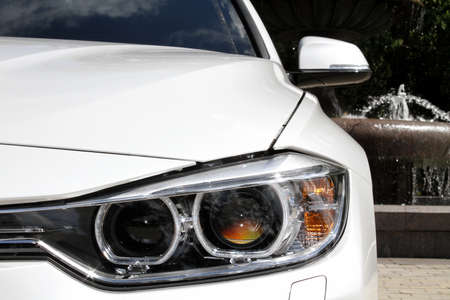 water repellent: Headlights of white car on the fountaine background Stock Photo