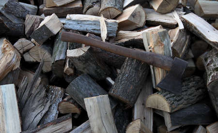 stack of firewood: Old axe on stack firewood oak logs Stock Photo