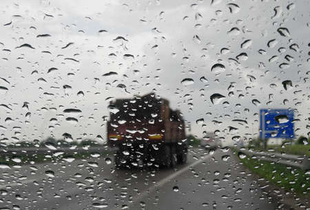 anti season: Look on truck on the highway through wet windshield with rain drops