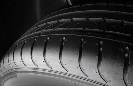 sidewall: Car parts shop. Tread blocks and grooves on new tire detailed