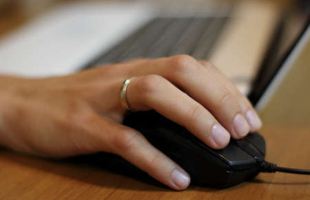 womans: Womans hand on the computer mouse at the office workplace Stock Photo