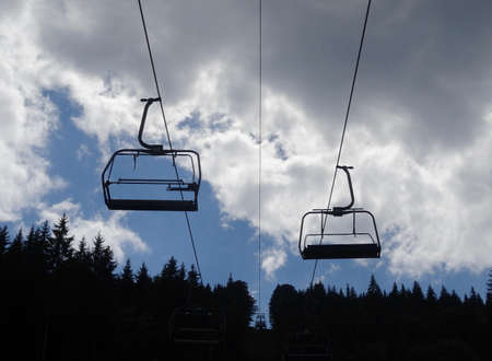 Two seats cable way over forest at mountain hill at summer time