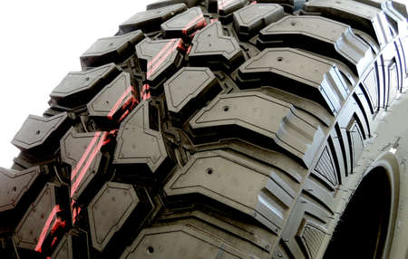 traction: Treads and sipes of mud terrain tire over white background