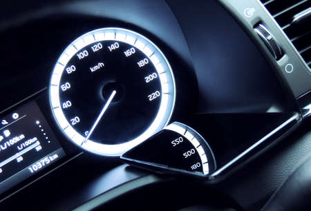 hands free phone: Phone charging on the car dashboard with digits reflection