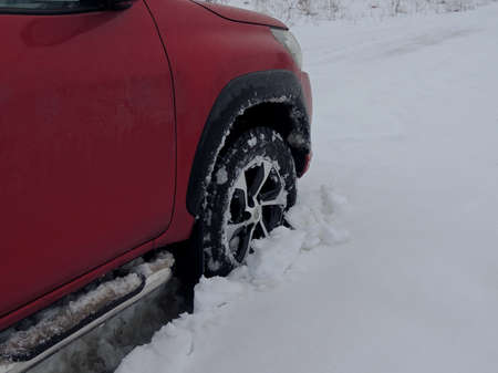 Cars wheel fell into the snow at winter off road travel