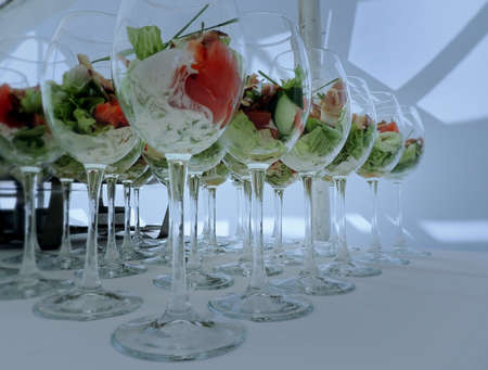 Salad cocktail with vegetable mix and white sauce in glasses on the food reception