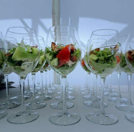 Salade fraîche et verrines de bacon servies sur nappe blanche Banque d'images