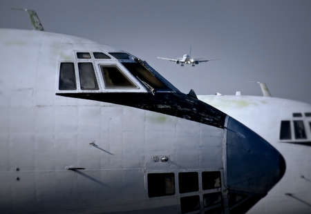 Modern Passenger Aircraft Landing Over Old Planes At The Airport Stock Photo