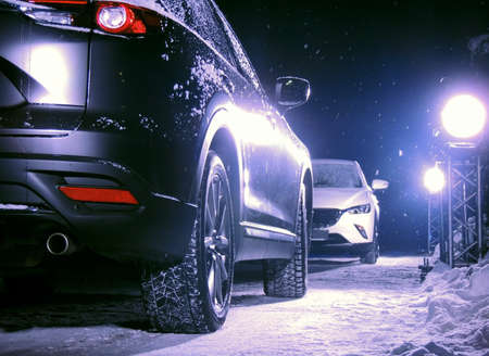 Black car in front of white car on the snowy road at night