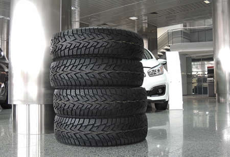 New car tires stacked up on the floor in front of car at service station