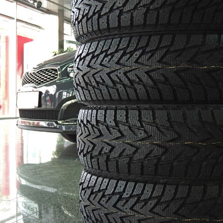 Stacked tires in front of the car in dealership showroom