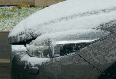 Side view of frozen car headlight covered with snow