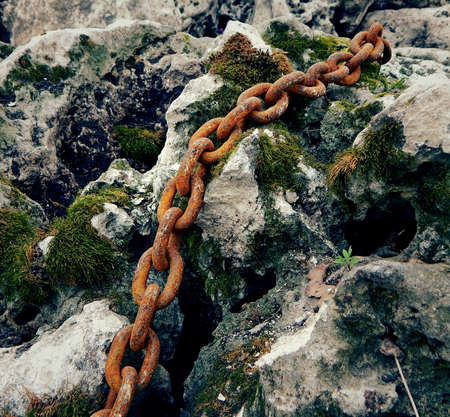 Rusty Metal Chain On The Old Reef Stone With Moss Stockfoto