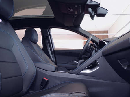 Front leather seats with blue read stitched in car Stockfoto