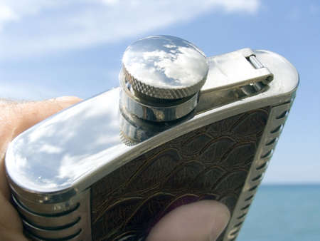 Flask with a wine in a cover reflection of the sky