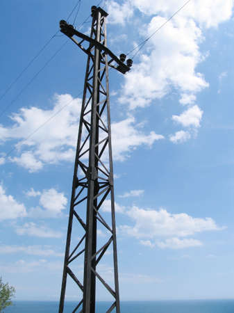 Electric mast on a background of the sea and the blue sky photo