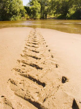 Trace of a tractor on river sand photo