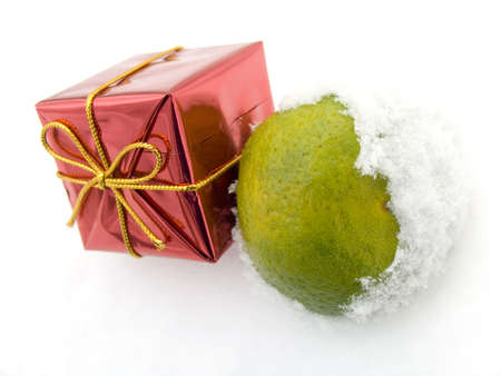 Tangerine and a christmas gift on snow in a winter snow-covered wood photo