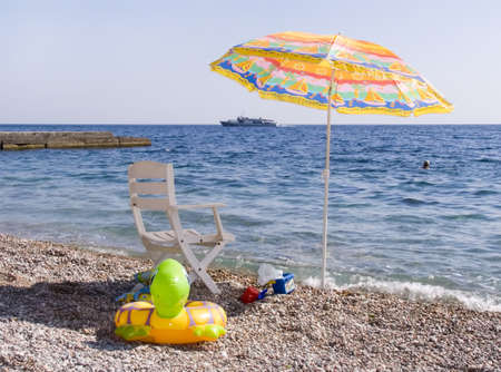 Beach parasol, chaise lounge, children's toys on a beach. On horizon a boat. Stock Photo - 643800
