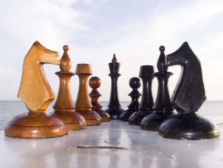 Combination from chessmen on a table with a kind on the sea Stockfoto