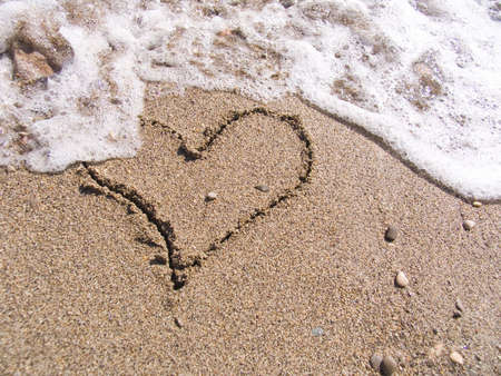 The inscription on sea sand as heart washes off a wave