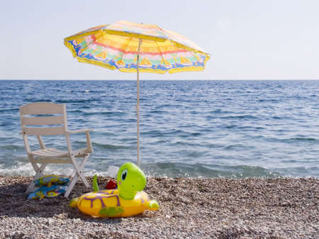 Beach parasol, chaise lounge, children's toys on a beach. On horizon a boat. Stock Photo - 643516