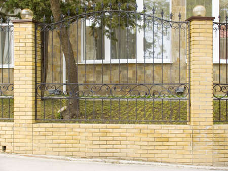 Fence of a house with a forged metal lattice