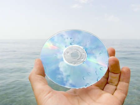 Computer disk in a hand on seacoast in drops of water Stock Photo