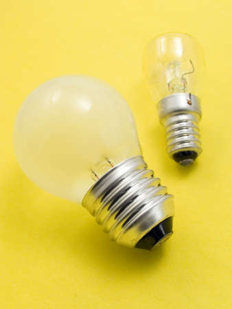 Small and big electric bulbs on a yellow background photo