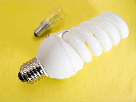 An energy efficient bulb and a small electric bulb on a yellow background photo