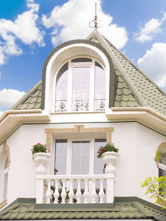 Cottage with a balcony on a background of the blue sky