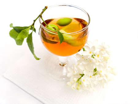 Branch with plum in a wine-glass with a red wine and a flower of a lilac