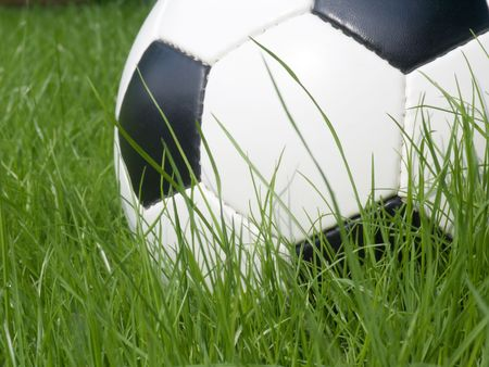 Soccer ball on a lawn from a green grass