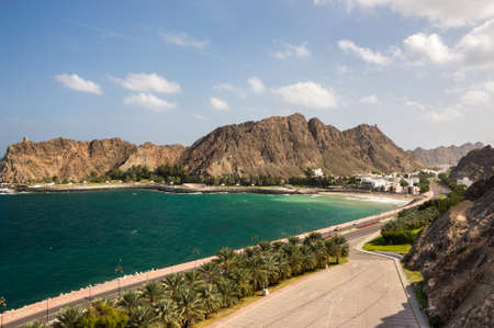 Coastline with a road and trees leading into Old Muscat