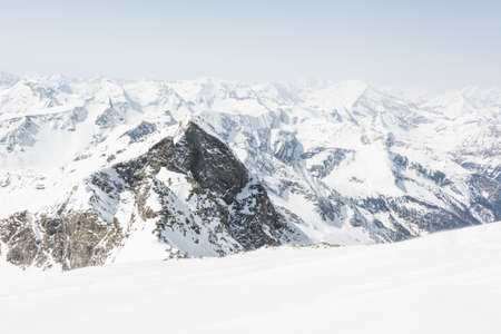 Snow covered slope in front of mountain ridge, view from Ankogel, Austria Stock Photo
