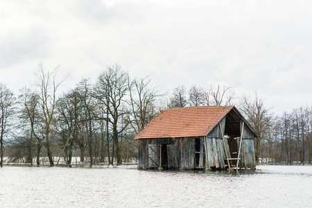 Barn surrounded with water after spring thaw photo
