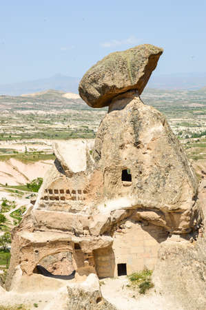 tilting: Cave dwelling with huge rock tilting on its top, Cappadocia, Turkey