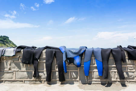 Diving suits drying on a brick wall with a sea view Stock Photo