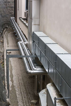 Metal ventilation pipes on a buildings facade photo
